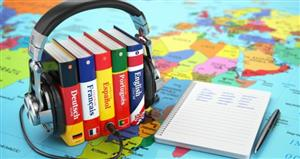 language dictionaries wearing headphones, map and notebook